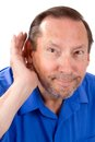Senior hard of hearing man with a loss cups his hand to his ear to help hear the sounds Royalty Free Stock Images