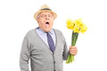 Senior having an allergic reaction to a bunch of tulips gentleman isolated on white background Royalty Free Stock Photo