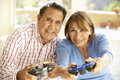 Senior Hispanic Couple Playing Video Game At Home Royalty Free Stock Photo