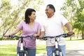 Senior Hispanic Couple Riding Bikes In Park Stock Images