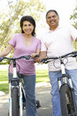 Senior Hispanic Couple Riding Bikes In Park Royalty Free Stock Photo