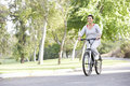Senior Hispanic Woman Cycling In Park Royalty Free Stock Photo