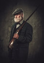 Senior hunter with a shotgun in a traditional shooting clothing, posing on a dark background. Royalty Free Stock Photo