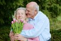 Senior husband giving bouquet of tulips to his wife happy loving caring couple outdoors a men pink beautiful Stock Photo
