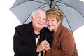 Senior husband wife cute and under an umbrella on white Royalty Free Stock Photo