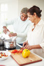 Senior indian couple cooking meal at home in kitchen Royalty Free Stock Photos