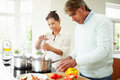 Senior indian couple cooking meal at home in kitchen cutting peppers Royalty Free Stock Image