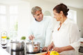 Senior indian couple cooking meal at home smiling each other Stock Image