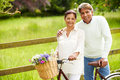 Senior indian couple on cycle ride in countryside with flowers basket smiling Stock Images