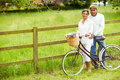 Senior indian couple on cycle ride in countryside looking at camera smiling Stock Photography