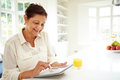 Senior indian woman using digital tablet at home in kitchen sitting down Stock Photos