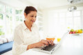 Senior Indian Woman Using Laptop Whilst Eating Breakfast Royalty Free Stock Photo