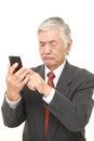Senior japanese businessman using smart phone looking confused studio shot of on white background Stock Photography