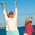 Senior ladies doing fitness exercises on beach close up portrait of two working out with weights Stock Photography
