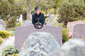 Senior lady in black at the grave of a loved one standing with folded hands looking over top gravestone Royalty Free Stock Photos