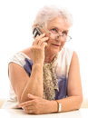Senior lady on cell phone talking looking up isolated sitting white table expression white background Stock Photography