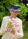 Senior lady holding a bouquet of fresh lilies as she stands in her green garden with wistful look nostalgia as she recalls Royalty Free Stock Photos