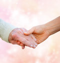 Senior lady holding hands with young woman on pink lights background Royalty Free Stock Photo