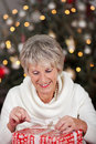 Senior lady opening her christmas gift beautiful stylish in front of the sparkling tree carefully untying the bow Royalty Free Stock Photo