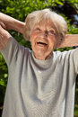 Senior lady with a sense of humour good having hearty laugh as she enjoys the sunshine outdoors in her garden on summer day Royalty Free Stock Photos