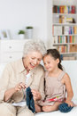 Senior lady teaching her granddaughter to knit as they relax together on the the sofa laughing together with enjoyment Royalty Free Stock Images