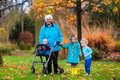 Senior lady with walker enjoying family visit happy a or wheel chair and children grandmother and kids a walk in the park child Royalty Free Stock Photography
