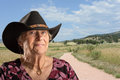 Senior lady wearing a black cowboy hat rural scene behind her Stock Photos