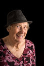 Senior lady wearing a fedora laughing isolated on black Royalty Free Stock Photo