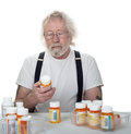 Senior looking at a bottle of pills with more bottles on table isolated on white Stock Photography