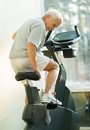 Senior ma in a fitness club man adjusting seat on bike machine Stock Photos