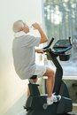 Senior ma in a fitness club man drinking while doing exercise on bike Royalty Free Stock Photos
