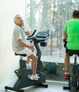 Senior ma in a fitness club tired man with towel on exercise bike Stock Photo