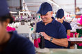 Senior machinist sewing happy in clothing factory Stock Image