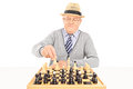 Senior making a move on a chessboard isolated white background Stock Photos
