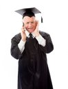 Senior male graduate trying to listen with talking on a mobile p phone Royalty Free Stock Images