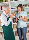 Senior male owner assisting female customer in choosing product grocery store Royalty Free Stock Photography
