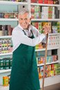 Senior male owner standing against shelves in portrait of happy with stick supermarket Royalty Free Stock Images