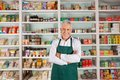 Senior male owner standing in supermarket portrait of happy arms crossed against shelves Stock Image