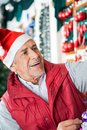 Senior male owner working at christmas store in santa hat Stock Photo