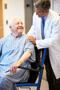 Senior male patient being pushed in wheelchair by doctor looking at each other smiling Stock Photography