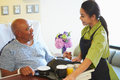 Senior male patient being served meal in hospital bed by carer smiling at each other Royalty Free Stock Photos