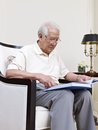 Senior man asian sitting in an armchair and reading Stock Images