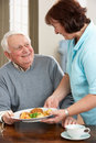 Senior Man Being Served Meal By Carer Stock Photo