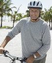 Senior man with bicycle on tropical beach portrait of happy wearing helmet Royalty Free Stock Image