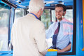 Senior man boarding bus and buying ticket from driver smiling at each other Stock Photography