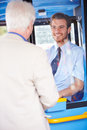 Senior man boarding bus and buying ticket looking at each other smiling Royalty Free Stock Image