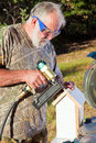 Senior Man Building a Bird House Stock Photo