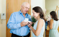 Senior man came to mature woman with gift men women at home Royalty Free Stock Photo