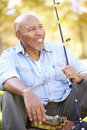 Senior man on camping holiday with fishing rod smiling Royalty Free Stock Photos