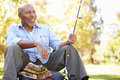 Senior man on camping holiday with fishing rod smiling Stock Image